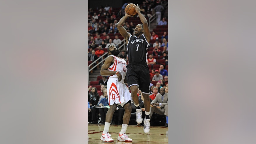 Houston Rockets' James Harden (13) leans away from Brooklyn Nets' Joe Johnson (7) who shoots in the first half of an NBA basketball game on Friday, Nov. 29, 2013, in Houston. (AP Photo/Pat Sullivan)