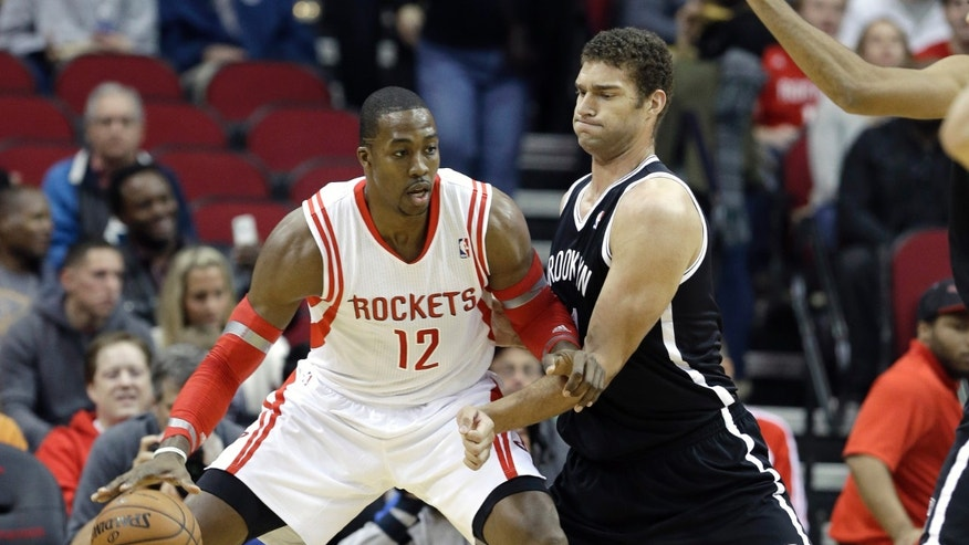Houston Rockets' Dwight Howard (12) pushes against Brooklyn Nets' Brook Lopez in the first half of an NBA basketball game on Friday, Nov. 29, 2013, in Houston. (AP Photo/Pat Sullivan)