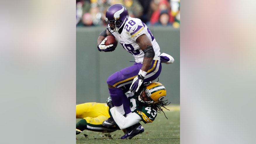 Green Bay Packers' M.D. Jennings tackles Minnesota Vikings' Adrian Peterson during the second half of an NFL football game Sunday, Nov. 24, 2013, in Green Bay, Wis. (AP Photo/Jeffrey Phelps)