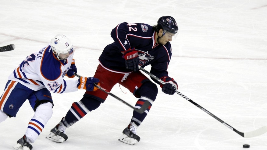 Columbus Blue Jackets' Artem Anisimov, right, of Russia, carries the puck in front of Edmonton Oilers' Jordan Eberle in the third period of an NHL hockey game in Columbus, Ohio, Friday, Nov. 29, 2013. Columbus won 4-2. (AP Photo/Paul Vernon)
