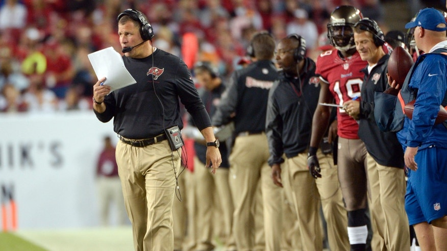 ADVANCE FOR WEEKEND EDITIONS, NOV. 30-DEC. 1 - FILE - In this Oct. 23, 2013, file photo, Tampa Bay Buccaneers head coach Greg Schiano, left, walks the sidelines during the first half of an NFL football game against the Carolina Panthers in Tampa, Fla. After spending the first half of the NFL season looking like a coach destined to be fired, he's led the Bucs to three straight victories. It's beginning to look like maybe he has the answers for turning around the struggling franchise. (AP Photo/Phelan M. Ebenhack, File)