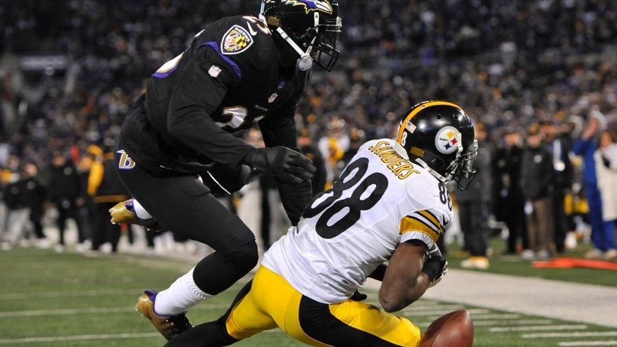 Pittsburgh Steelers wide receiver Emmanuel Sanders is unable to hold on to the ball for a 2-point conversion as he is pressured by Baltimore Ravens defensive back Chykie Brown in the second half of an NFL football game, Thursday, Nov. 28, 2013, in Baltimore. Baltimore won 22-20. (AP Photo/Gail Burton)
