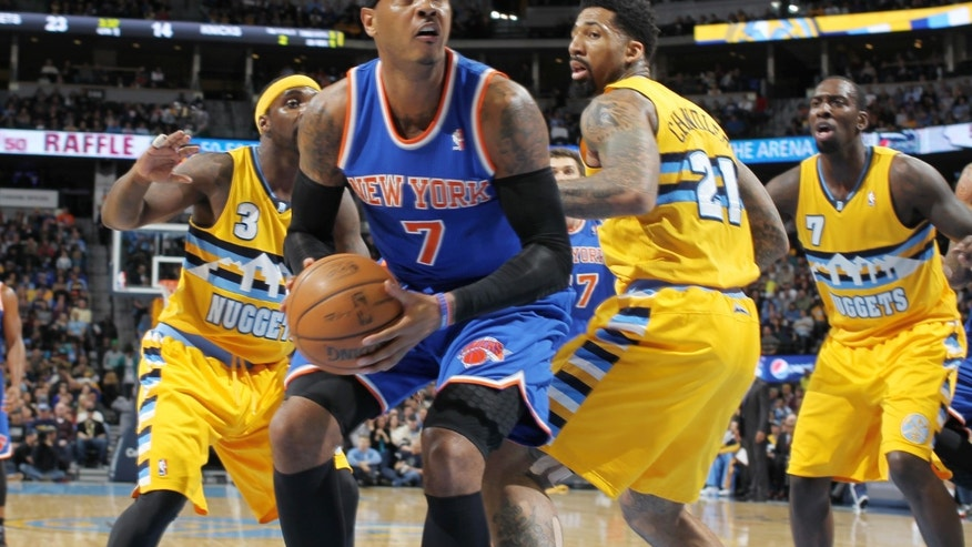 New York Knicks forward Carmelo Anthony, front, goes up to shoot as Denver Nuggets, from back left, guard Ty Lawson and forwards Wilson Chandler and J.J. Hickson cover in the first quarter of an NBA basketball game in Denver, Friday, Nov. 29, 2013. (AP Photo/David Zalubowski)