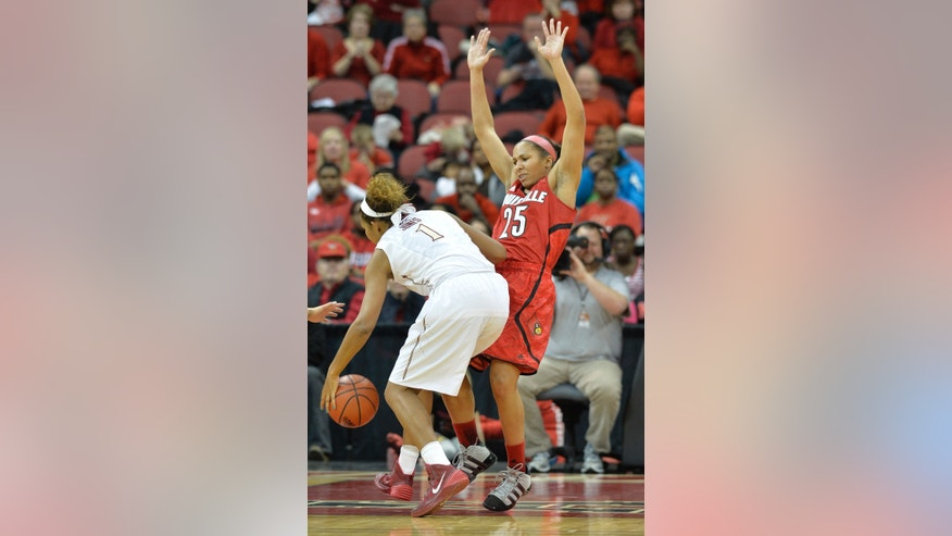 Louisville's Tia Gibbs, right, takes a charge from Florida State's Kai James during the second half of an NCAA college basketball game on Sunday Nov. 24, 2013, in Louisville, Ky. Louisville defeated Florida State in overtime 69-59.  (AP Photo/Timothy D. Easley)