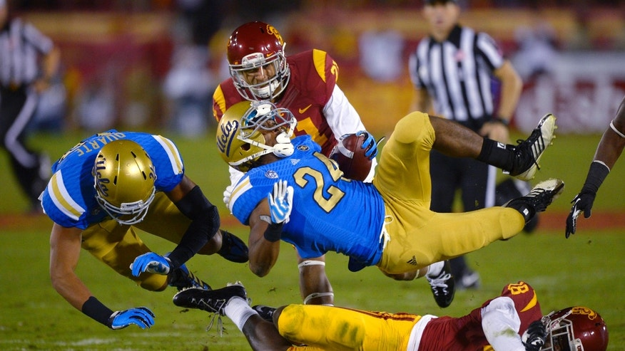 UCLA running back Paul Perkins (24) falls over Southern California safety Dion Bailey (18) as wide receiver Thomas Duarte, left, falls and safety Su'a Cravens gives chase during the first half of an NCAA college football game, Saturday, Nov. 30, 2013, in Los Angeles. (AP Photo/Mark J. Terrill)