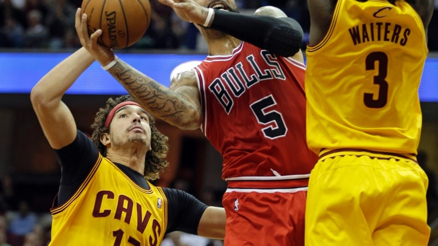 Chicago Bulls' Carlos Boozer (5) shoots against Cleveland Cavaliers' Anderson Varejao, left, of Brazil, and Dion Waiters (3) in the first quarter of an NBA basketball game Saturday, Nov. 30, 2013, in Cleveland. (AP Photo/Mark Duncan)
