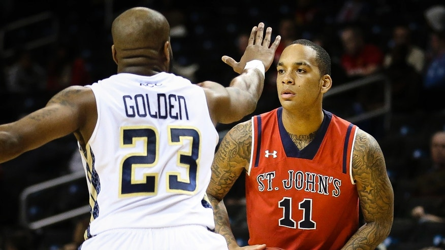 St. John's guard D'Angelo Harrison (11) looks to pass against Georgia Tech guard Trae Golden (23) in the first half of their NCAA college basketball game, the consolation game of the Barclays Center Classic, Saturday, Nov. 30, 2013, in New York. (AP Photo/John Minchillo)