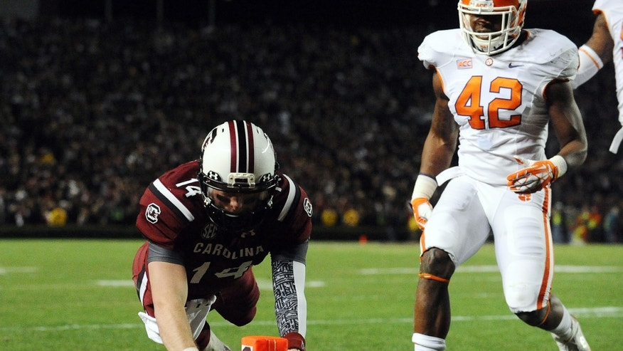 South Carolina quarterback Connor Shaw (14) dives into the end zone for a touchdown as Clemson linebacker Stephone Anthony (42) defends during the first half of an NCAA college football game on Saturday, Nov. 30, 2013, in Columbia, S.C. (AP Photo/Rainier Ehrhardt)