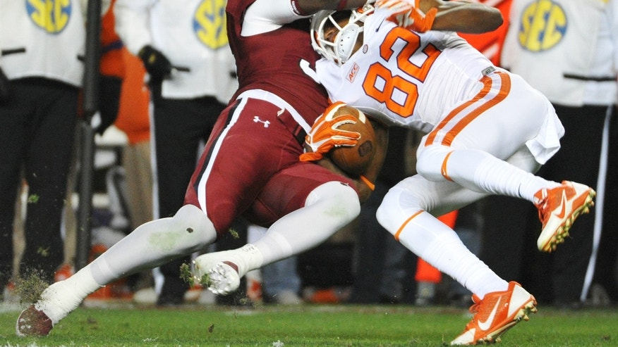 South Carolina linebacker Larenz Bryant (32) tackles Clemson wide receiver T.J. Green (82) during the opening kickoff of an NCAA college football game on Saturday, Nov. 30, 2013, in Columbia, S.C. (AP Photo/Rainier Ehrhardt)