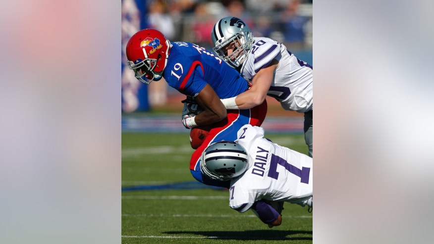 Kansas wide receiver Justin McCay (19) is tackled by Kansas State defensive backs Kip Daily (7) and Dylan Schellenberg (20) during the first half of an NCAA college football game in Lawrence, Kan., Saturday, Nov. 30, 2013. (AP Photo/Orlin Wagner)