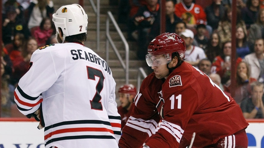Phoenix Coyotes center Martin Hanzal (11) cross checks Chicago Blackhawks defenseman Brent Seabrook (7) in the second period during an NHL hockey game on Saturday, Nov. 30, 2013, in Glendale, Ariz. (AP Photo/Rick Scuteri)