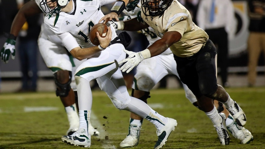 Central Florida linebacker Justin McDonald (34) chases South Florida quarterback Mike White (14) during the second half of an NCAA college football game on Friday, Nov. 29, 2013, in Orlando, Fla. UCF won 23-20. (AP Photo/Reinhold Matay)