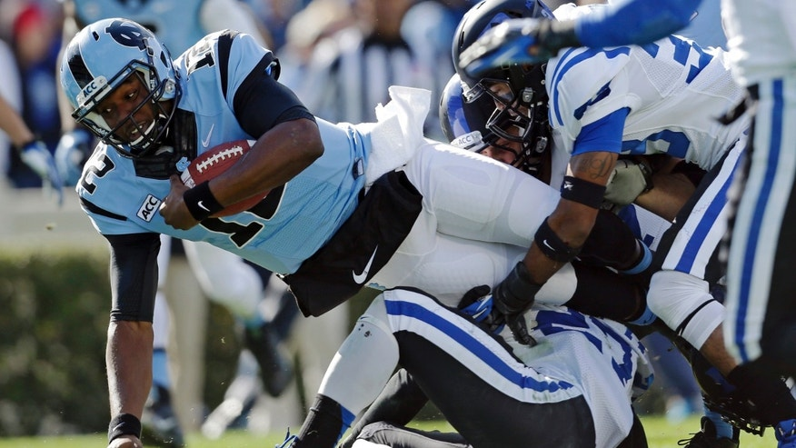 North Carolina quarterback Marquise Williams (12) dives for yardage as Duke's DeVon Edwards, bottom, and Deondre Singleton make the tackle during the first half of an NCAA college football game in Chapel Hill, N.C., Saturday, Nov. 30, 2013. (AP Photo/Gerry Broome)