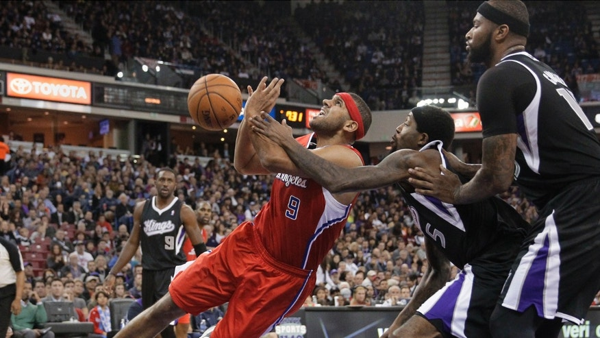 Los Angeles Clippers forward Jared Dudley, left, is fouled by Sacramento Kings forward John Salmons, center, while Kings' DeMarcus Cousins, right, watches during the first quarter of an NBA basketball game in Sacramento, Calif., Friday, Nov. 29, 2013. (AP Photo/Rich Pedroncelli)