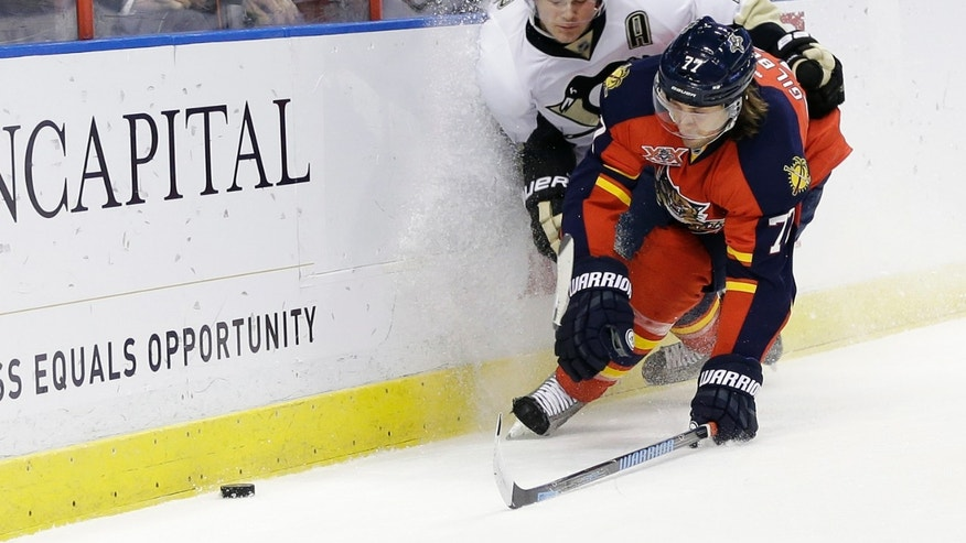 Pittsburgh Penguins left wing Chris Kunitz, left, and Florida Panthers' Tom Gilbert (77) go for the puck during the first period of an NHL hockey game Saturday, Nov. 30, 2013, in Sunrise, Fla. (AP Photo/Lynne Sladky)