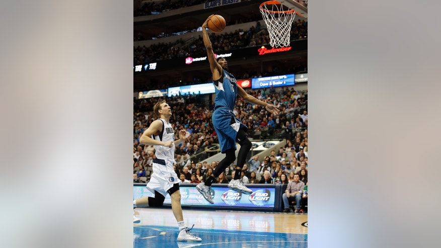 Minnesota Timberwolves forward Corey Brewer (13) dunks the ball on a break away as Dallas Mavericks Dirk Nowitzki (41) looks on during the first half of an NBA basketball game Saturday, Nov. 30, 2013, in Dallas. (AP Photo/Brandon Wade)
