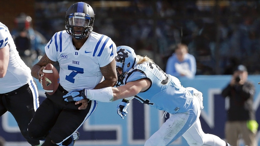 Duke quarterback Anthony Boone (7) runs the ball as North Carolina's Jeff Schoettmer looks for the tackle during the first half of an NCAA college football game in Chapel Hill, N.C., Saturday, Nov. 30, 2013. (AP Photo/Gerry Broome)