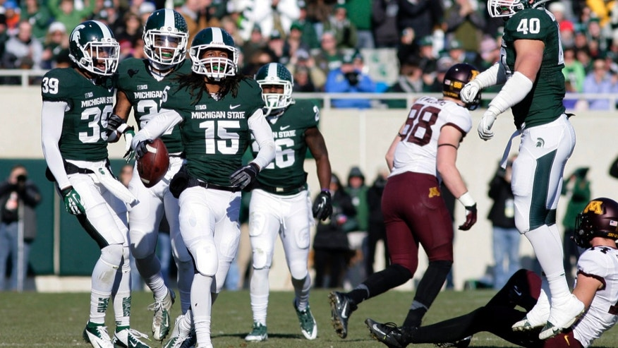 Michigan State players, including Jermaine Edmondson (39), Kurtis Drummond, Trae Waynes (15), R.J. Williamson (26) and Max Bullough (40), celebrate Waynes' interception against Minnesota during the second quarter of an NCAA college football game, Saturday, Nov. 30, 2013, in East Lansing, Mich. (AP Photo/Al Goldis)