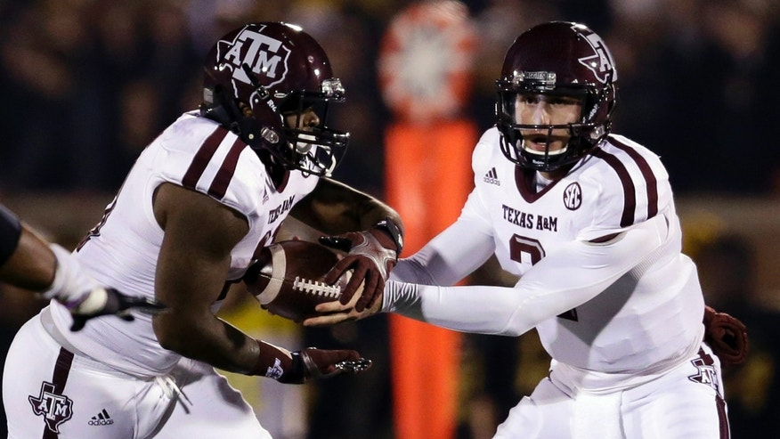 Texas A&M quarterback Johnny Manziel, right, hands off to running back Tra Carson as Carson rushes for a 29-yard touchdown during the first quarter of an NCAA college football game against Missouri, Saturday, Nov. 30, 2013, in Columbia, Mo. (AP Photo/Jeff Roberson)
