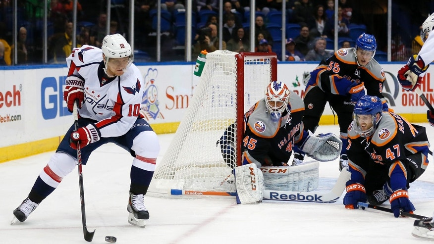 Washington Capitals left wing Martin Erat (10) circles the net looking to pass as New York Islanders goalie Anders Nilsson (45) and Andrew MacDonald (47) defend during the first period of an NHL hockey game in Uniondale, N.Y., Saturday, Nov. 30, 2013. (AP Photo/Paul J. Bereswill)