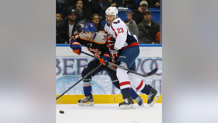 Washington Capitals defenseman Tyson Strachan (23) holds back New York Islanders center Pierre-Marc Bouchard (96) while going for the puck during the first period of an NHL hockey game in Uniondale, N.Y., Saturday, Nov. 30, 2013. (AP Photo/Paul J. Bereswill)