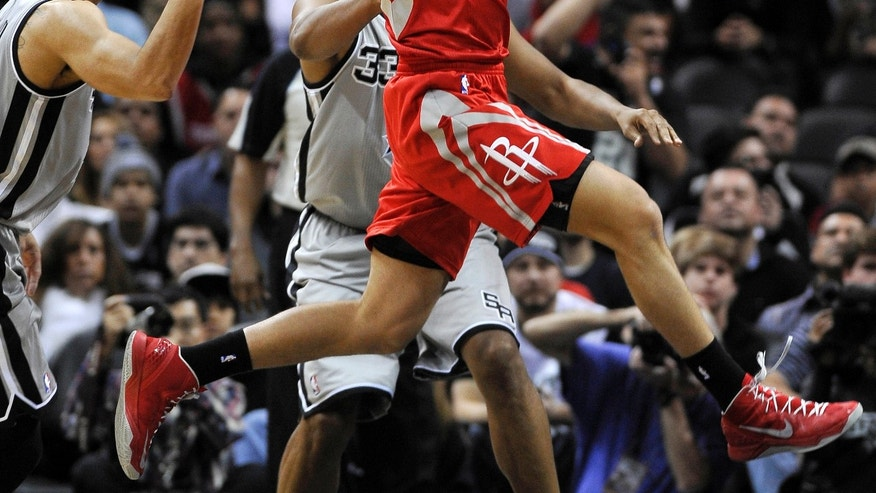 Houston Rockets forward Chandler Parsons passes around San Antonio Spurs shooting guard Danny Green, left, during the first half of an NBA basketball game Saturday, Nov. 30, 2013, in San Antonio. (AP Photo/Darren Abate)