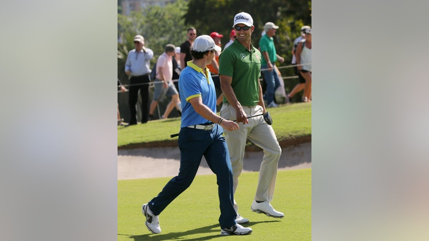 Rory McIlroy, left, of Northern Ireland walks with Australia's Adam Scott during their third round at the Australian Open Golf tournament in Sydney, Australia, Saturday, Nov. 30, 2013.(AP Photo/Rob Griffith)