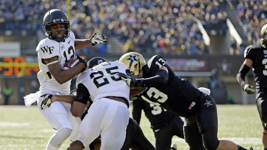 Wake Forest wide receiver Tyree Harris (12) is knocked out-of-bounds by Vanderbilt defenders including Jake Sealand (13) in the first quarter of an NCAA college football game on Saturday, Nov. 30, 2013, in Nashville, Tenn. Blocking for Harris is Wake Forest running back Josh Harris (25). (AP Photo/Mark Humphrey)