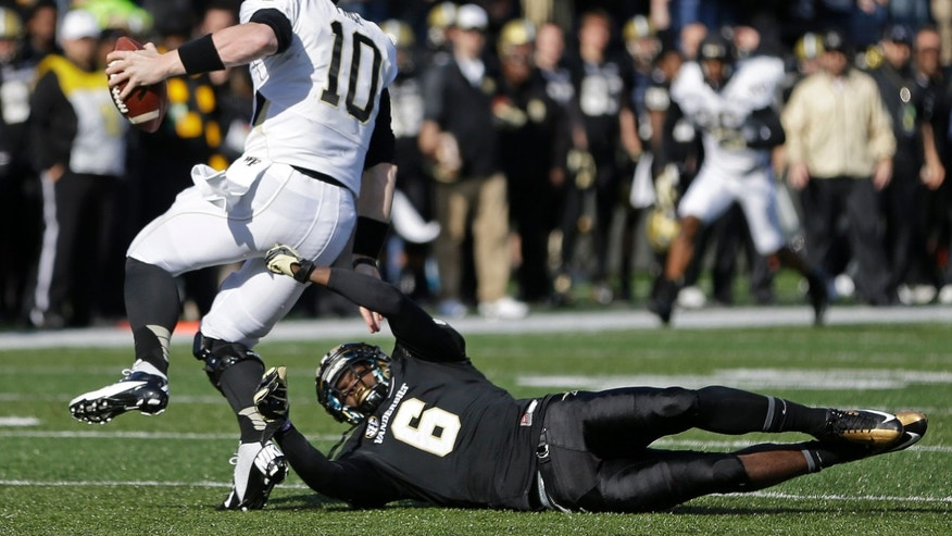 Wake Forest quarterback Tanner Price (10) scrambles away from Vanderbilt defender Darrius Sims (6) in the first quarter of an NCAA college football game on Saturday, Nov. 30, 2013, in Nashville, Tenn. (AP Photo/Mark Humphrey)
