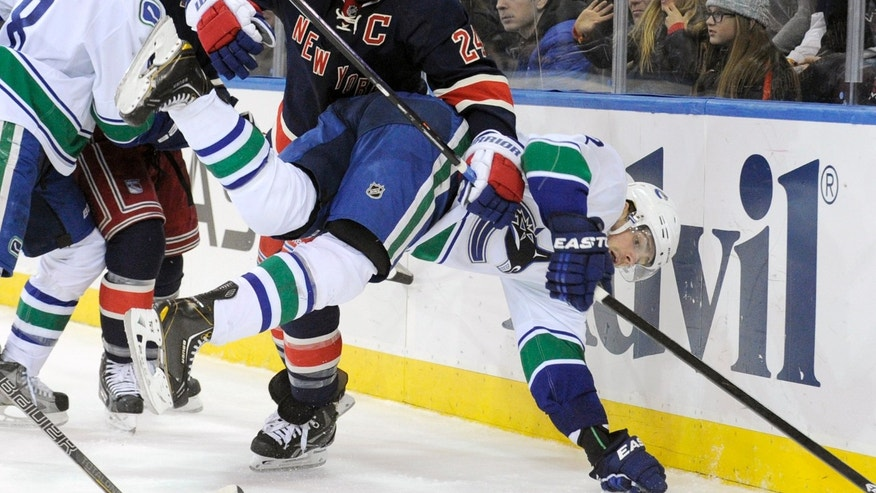 New York Rangers' Ryan Callahan (24) checks Vancouver Canucks' Dan Hamhuis during the second period of an NHL hockey game Saturday, Nov. 30, 2013, at Madison Square Garden in New York. (AP Photo/Bill Kostroun)