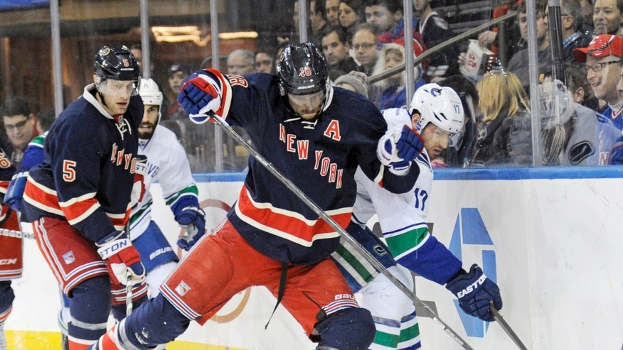 New York Rangers' Marc Staal (18) checks Vancouver Canucks' Ryan Kesler during the first period of an NHL hockey game Saturday, Nov. 30, 2013, at Madison Square Garden in New York. (AP Photo/Bill Kostroun)
