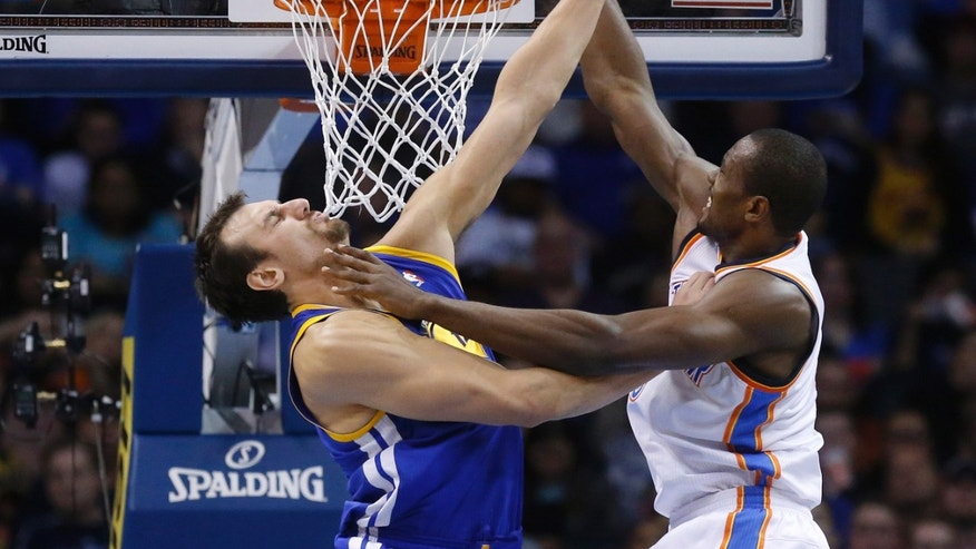 Oklahoma City Thunderforward Serge Ibaka, right, dunks in front of Golden State Warriors center Andrew Bogut (12) in the second quarter of an NBA basketball game in Oklahoma City, Friday, Nov. 29, 2013. (AP Photo/Sue Ogrocki)