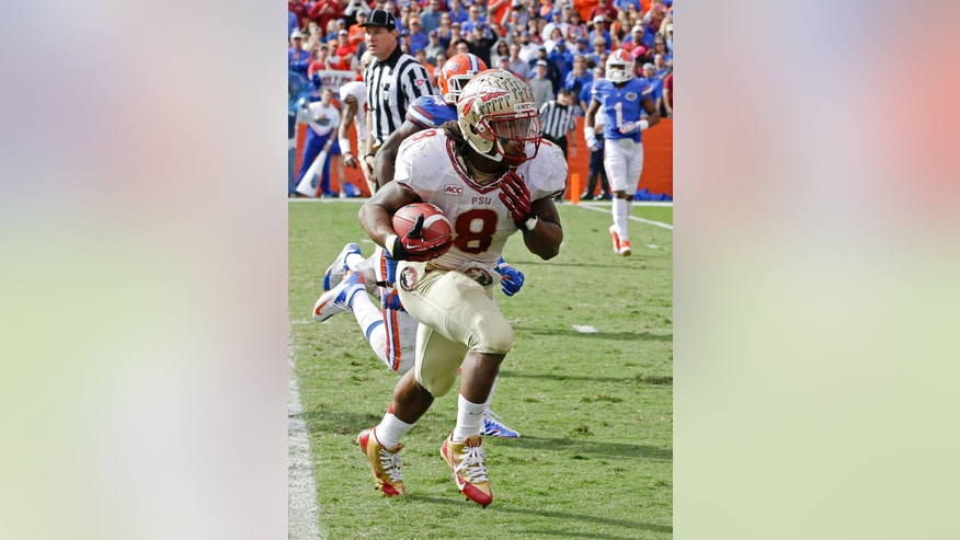 Florida State running back Devonta Freeman (8) runs past the Florida defense for an 11-yard touchdown run during the second half of an NCAA college football game in Gainesville, Fla., Saturday, Nov. 30, 2013.(AP Photo/John Raoux)
