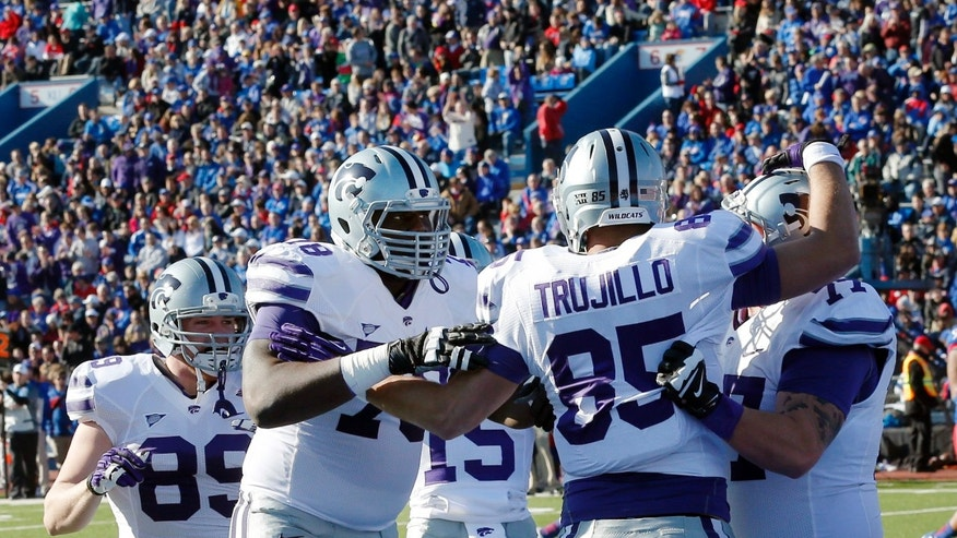 Kansas State tight end Zach Trujillo (85) is congratulated by teammates following his touchdown during the first half of an NCAA college football game against Kansas in Lawrence, Kan., Saturday, Nov. 30, 2013. (AP Photo/Orlin Wagner)
