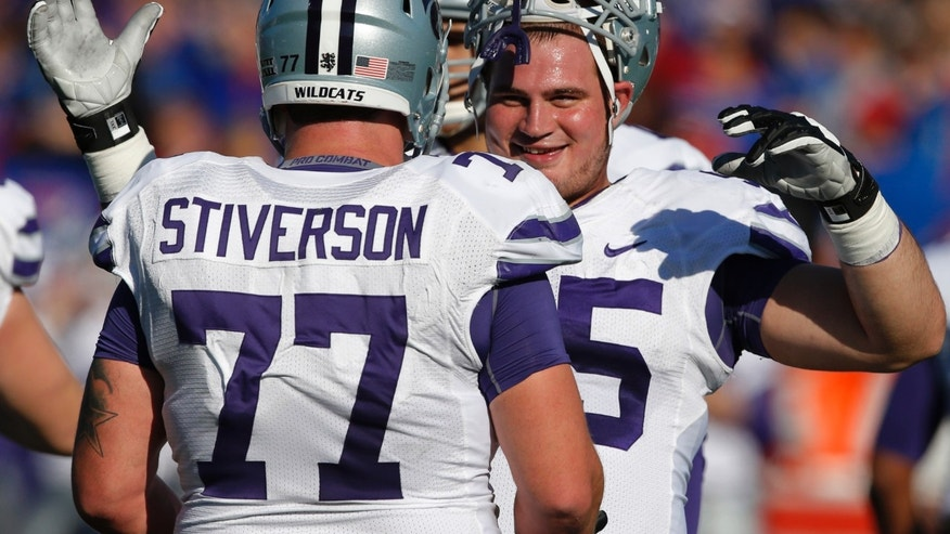 Kansas State offensive linesmen Cody Whitehair (55) and Boston Stiverson (77) celebrate a touchdown during the second half of an NCAA college football game against Kansas in Lawrence, Kan., Saturday, Nov. 30, 2013. Kansas State defeated Kansas 31-10. (AP Photo/Orlin Wagner)