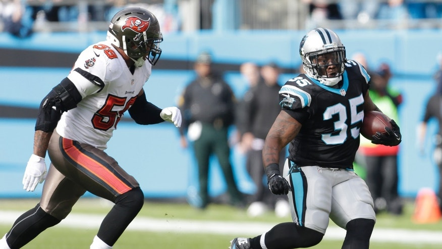 Carolina Panthers' Mike Tolbert (35) runs past Tampa Bay Buccaneers' Mason Foster (59) in the first half of an NFL football game in Charlotte, N.C., Sunday, Dec. 1, 2013. (AP Photo/Bob Leverone)