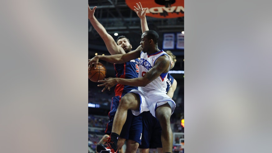 Philadelphia 76ers guard James Anderson, right, passes the ball against Detroit Pistons forward Josh Harrellson, left, during the first half of an NBA basketball game on Sunday, Dec. 1, 2013, in Auburn Hills, Mich. (AP Photo/Duane Burleson)