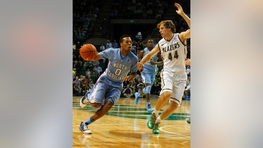 North Carolina guard Nate Britt, left, drives to the basket around UAB forward Jordan Swing (44) during the first half of an NCAA college basketball game on Sunday, Dec. 1, 2013, in Birmingham, Ala. (AP Photo/Butch Dill)
