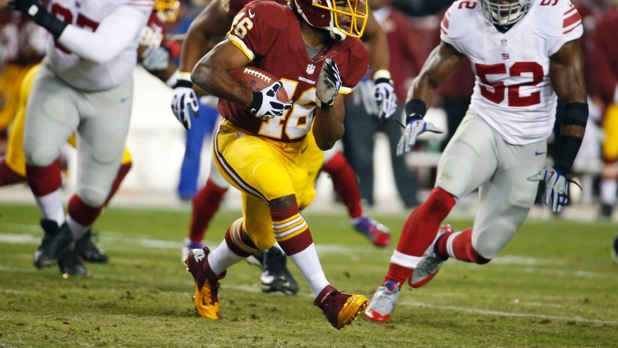 Washington Redskins running back Alfred Morris (46) tries to avoid being tackled by New York Giants middle linebacker Jon Beason (52) during an NFL football game Sunday, Dec. 1, 2013, in Landover, Md. (AP Photo/Alex Brandon)