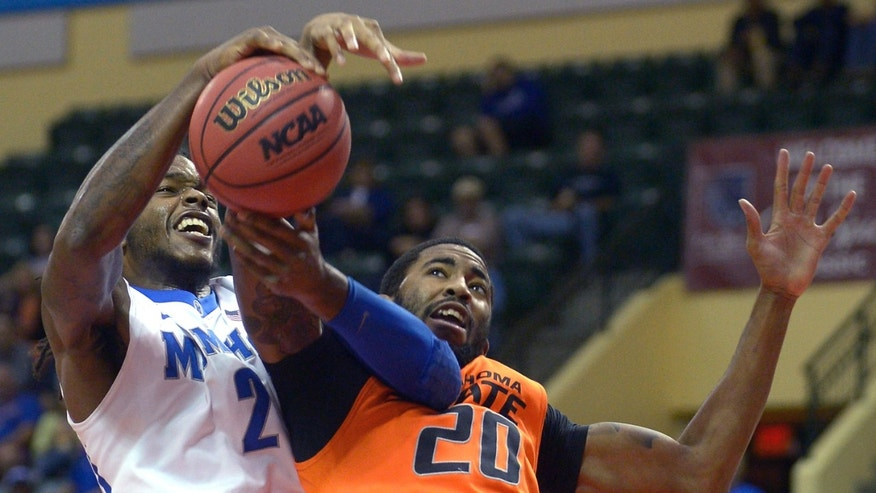 Memphis forward Shaq Goodwin, left, and Oklahoma State forward Michael Cobbins battle for a rebound during the first half of an NCAA college basketball game at the Old Spice Classic tournament in Kissimmee, Fla., Sunday, Dec. 1, 2013.(AP Photo/Phelan M. Ebenhack)