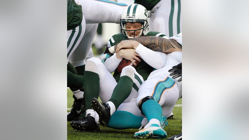 New York Jets quarterback Matt Simms, center, is sacked by Miami Dolphins outside linebacker Koa Misi during the second half of an NFL football game on Sunday, Dec. 1, 2013, in East Rutherford, N.J. (AP Photo/Seth Wenig)