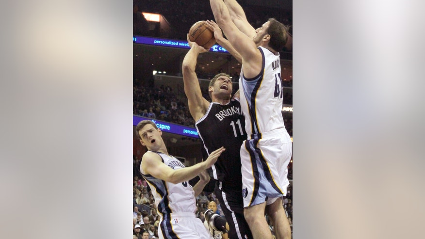 Brooklyn Nets' Brook Lopez (11) goes to the basket between Memphis Grizzlies' Kosta Koufos (41) and Jon Leuer, left, in the first half of an NBA basketball game in Memphis, Tenn., Saturday, Nov. 30, 2013. (AP Photo/Danny Johnston)