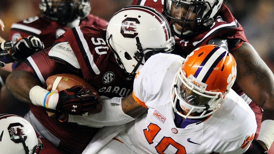 South Carolina defensive end Chaz Sutton (90) strips the ball from Clemson quarterback Tajh Boyd (10) to cause a fumble during the second half of an NCAA college football game on Saturday, Nov. 30, 2013, in Columbia, S.C. South Carolina won 31-17. (AP Photo/Richard Shiro)