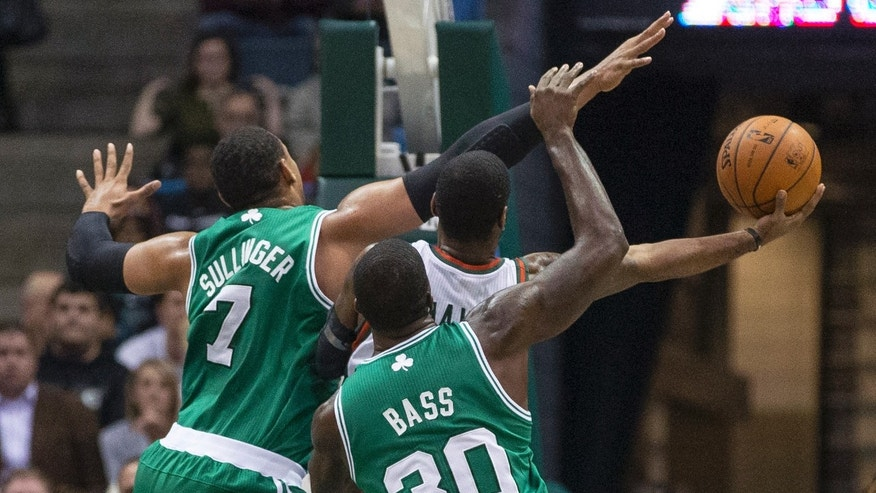 Milwaukee Bucks' O.J. Mayo is covered by Boston Celtics' Jared Sullinger and Brandon Bass during the first half of an NBA basketball game Saturday, Nov. 30, 2013, in Milwaukee. (AP Photo/Tom Lynn)