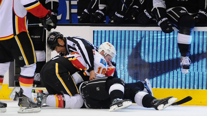 Linesman Jay Sharrers (57) attempts to break up a fight between Calgary Flames center Matt Stajan (18) and Los Angeles Kings right wing Dustin Brown, bottom, during the second period of an NHL hockey game, Saturday, Nov. 30, 2013, in Los Angeles. (AP Photo/Gus Ruelas)