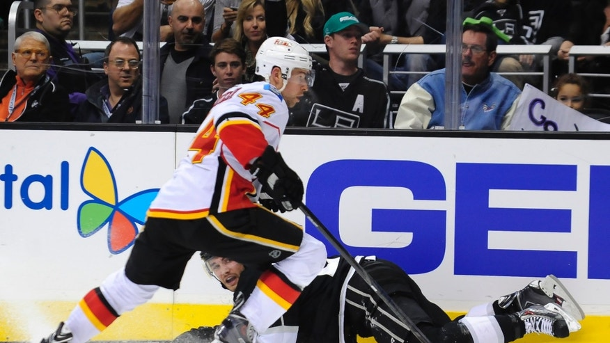 Calgary Flames defenseman Chris Butler (44) goes for the puck after Los Angeles Kings defenseman Alec Martinez fell to the ice during the second period of an NHL hockey game, Saturday, Nov. 30, 2013, in Los Angeles. (AP Photo/Gus Ruelas)