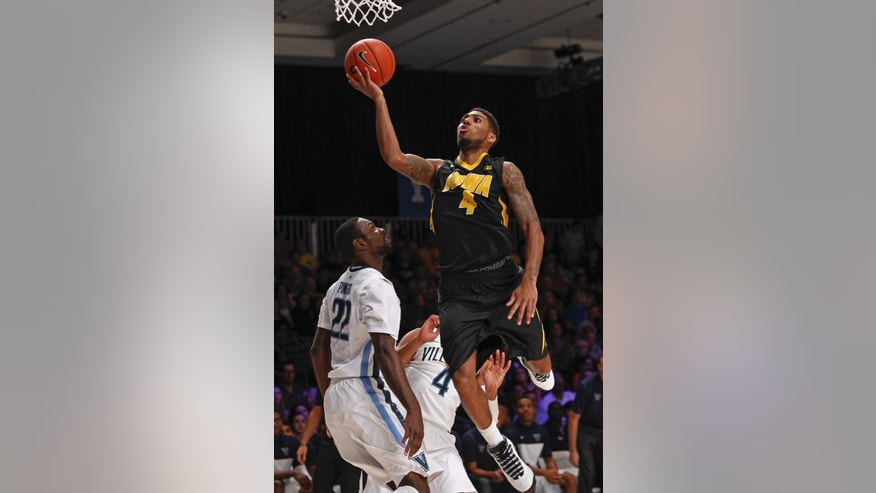 Iowa's Roy Devyn Marble, right, drives for a layup as Villanova's JayVaughn Pinkston, left, and Darrun Hilliard look on during the first half of an NCAA college basketball game in Paradise Island, Bahamas, Saturday, Nov. 30, 2013. (AP Photo/Bahamas Visual Services, Tim Aylen)