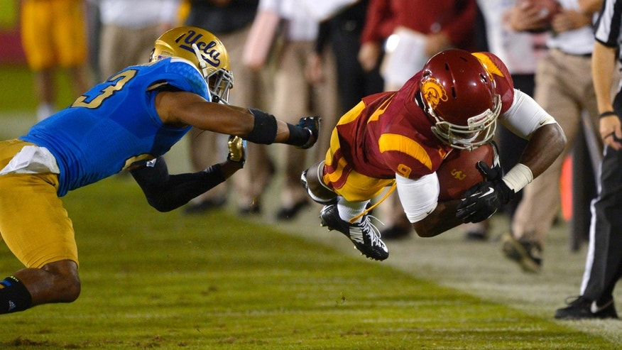 Southern California wide receiver Marqise Lee, right, dives for extra yards as UCLA cornerback Anthony Jefferson defends during the second half of an NCAA college football game, Saturday, Nov. 30, 2013, in Los Angeles. UCLA won 35-14. (AP Photo/Mark J. Terrill)