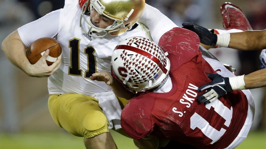 Notre Dame quarterback Tommy Rees, left, is sacked by Stanford linebacker Shayne Skov during the second half of an NCAA college football game on Saturday, Nov. 30, 2013, in Stanford, Calif. Stanford won 27-20. (AP Photo/Marcio Jose Sanchez)