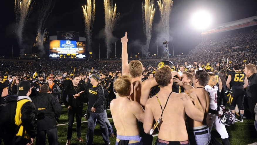 Fans celebrate on the field following Missouri's 28-21 victory over Texas A&M in an NCAA college football game on Saturday, Nov. 30, 2013, in Columbia, Mo. (AP Photo/L.G. Patterson)